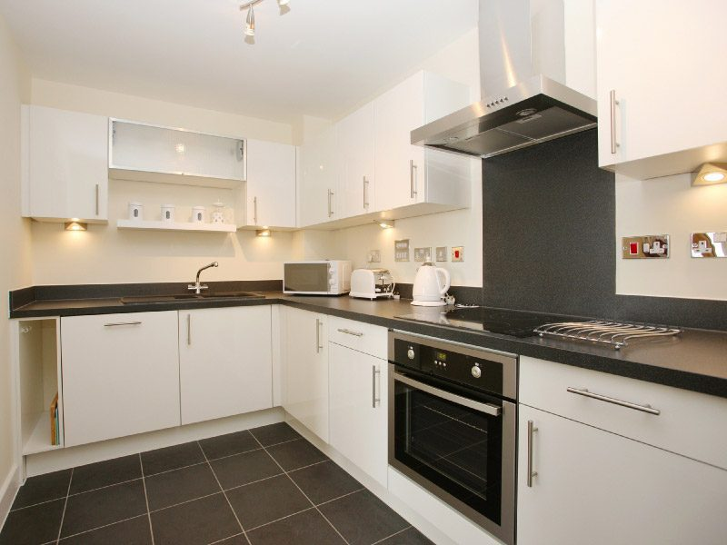 Modern fitted kitchen with white units and a granite worktop